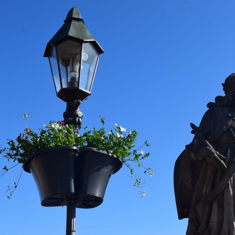 Flower Basket an Laterne neben Heiligenfigur