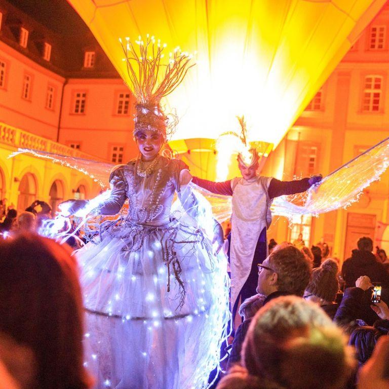 Stelzenläufer vor beleuchteter Kulisse in Würzburg