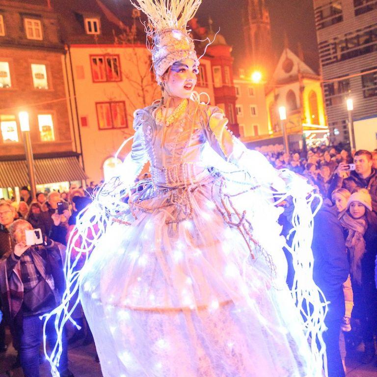 Geschmückte Stelzenläuferin beim Lichterglanz in Würzburg